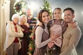 Happy young family of three standing in front of camera on background of mature adults by Christmas  poster