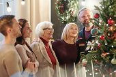 Happy family of five adults looking at decorated Christmas tree while standing in front of it at hom poster