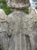 Scene In A Cemetery: Close Up Of A Stone Statue Of An Angel Seen From The Back. The Statue Is Old An poster