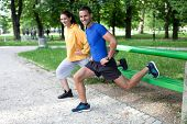 Happy Young Couple Exercising Outdoors, Using A Park Bench To Do A Leg Exercise