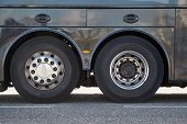 Bus wheels on the back axles of a long distance tour bus poster