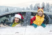 Toward adventure! Happy family are relaxing and enjoying road trip. Mother, child and car on snowy w poster