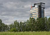 pic of urbanisation  - Modern skyscraper appearing behind meadows and trees - JPG