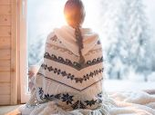 Woman wearing nordic style poncho sitting home by the window with cup of coffee, winter woods landsc poster