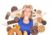 image of starving  - A woman has sweet food snacks around her on a white background - JPG