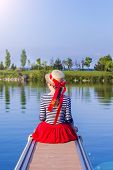 Beautiful Girl In A Straw Hat On The Pier From The Back. Girl In A Red Skirt And A Sailor Suit On Th poster