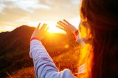 Carefree hipster girl enjoying nature on top of mountain with sunset. Image of freedom concept. Hike poster