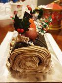 Close-up Side Image Of Brown Creamy Yule Log Dessert Christmas Cake With Decoration In Foreground On poster