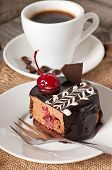 Sweet dessert fruitcake with a cherry and a cup of coffee