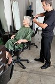Male hairdresser straightening senior woman's hair in beauty salon