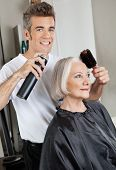Portrait of male hairdresser with hairspray and hairbrush setting up female customer's hair at beaut