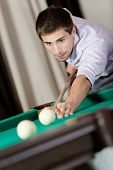 Young male playing billiard. Spending free time on gambling