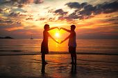 Couple holding hands heart-shaped on the sea beach at sunset.