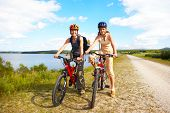 image of road trip  - Mother and a daughter cycling near the lake - JPG