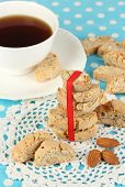 Aromatic cookies cantuccini and cup of coffee on blue tablecloth close-up