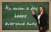 Teacher Showing An Onion A Day Keeps Everyone Away On Blackboard