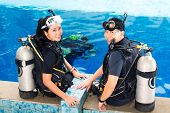 stock photo of oxygen  - Asian people at the diver Course in diving school in wetsuit with an oxygen tank - JPG