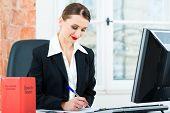 Junger Anwalt arbeiten in ihrem Büro, sie sitzt hinter Ordner in eine Datei schreiben