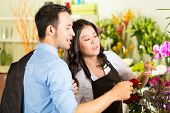 Friendly Asian florist or Saleswoman in a flower shop advising a customer