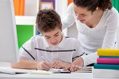 stock photo of brother sister  - older sister helps brother with a homework - JPG