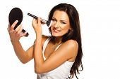 Beautiful woman applying blusher to her cheek with a large cosmetics brush while holding a compact mirror in front of her isolated on white