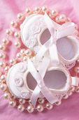 Overhead of white baby booties with string of pearls on pink blanket