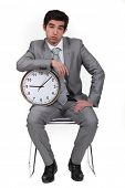 Businessman bored with alarm clock