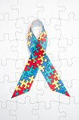 image of autism  - Awareness ribbon for autism and aspergers on white jigsaw background - JPG