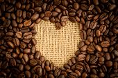 Heart shaped indent in pile of coffee beans on burlap sack