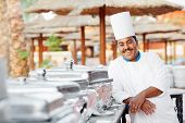 Adult arab chef man in uniform with food on cooker in resort hotel restaurant kitchen