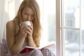 Young girl on the window sill in my pajamas with a cup of reading a book