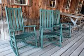 Three green rocking chairs on porch