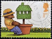 A stamp printed in Great Britain shows Bear pulling Potted Topiary Tree (Moving Home)