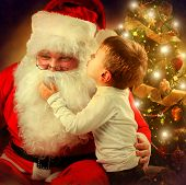 Santa Claus and Little Boy. Christmas Scene. Boy Telling Wish in Santa Claus's Ear in front of Chris
