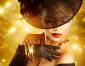 Glamour Woman Portrait over Holiday Gold Background.Luxury Golden Jewelry. Gorgeous Vogue Style Lady