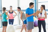 Fit couple with friends standing in background in bright exercise room