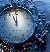 Christmas clock over snow wooden background. Five to twelve.