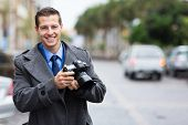 handsome journalist holding a camera in the city in the rain