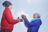 Two young people playing with snow