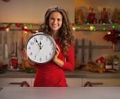 Happy Young Housewife Showing Clock In Christmas Decorated Kitch