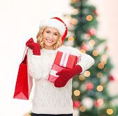 shopping, sale, gifts, christmas, x-mas concept - smiling woman in santa helper hat with shopping ba