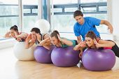 Class exercising on fitness balls as trainer helps one at a bright gym