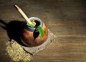 Calabash and bombilla with yerba mate on grey wooden background
