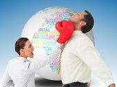 Composite image of businesswoman hitting a businessman with boxing gloves