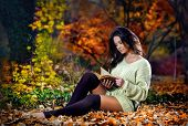 Young Caucasian sensual woman reading a book in a romantic autumn scenery