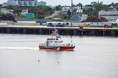 picture of coast guard  - Canadian Coast Guard boat cruising past industrial area on coast of Canada - JPG