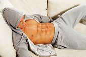 Sporty man in grey hoodie with muscular torso relaxing on sofa