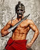 stock photo of sword  - Gladiator with muscular body with sword and helmet - JPG