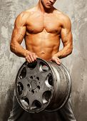 stock photo of muscle-car  - Handsome sporty man with muscular body holding alloy wheel - JPG