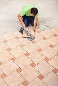 Man Laying Ceramic Floor Tiles